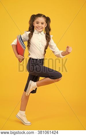 An Inspirational Literature. Adorable Little Girl Running With Books Of English Literature On Yellow