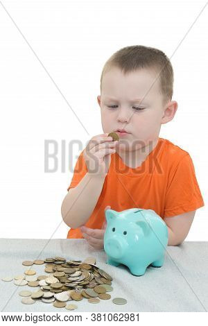 Little Boy In An Orange T-shirt On A White Background Examines And Puts Coins In A Piggy Bank. Verti
