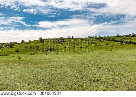 A Hill With Green Grass, Bushes And Trees Against A Blue Sky With White Clouds. Horizon, Serenity. H
