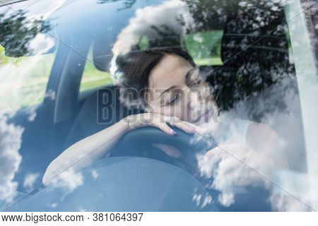 Young Female Driver At The Wheel Of Her Car, Very Tired, Falling Asleep While Driving In A Potential