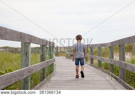 Child Is Alone On The Road. Boy Is Lost And Goes Forward. Boy Wants To Be Alone. Back View Of A Chil