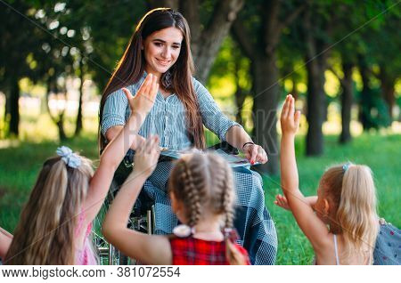 Disabled Teacher Conducts A Lesson With Children In Nature. Interaction Of A Teacher In A Wheelchair