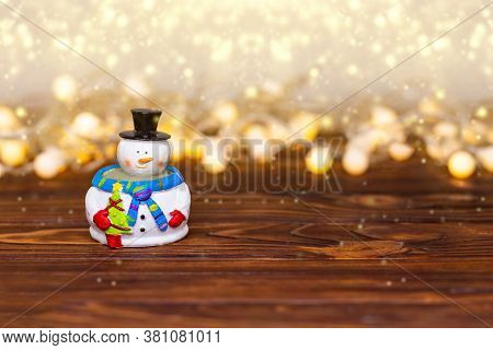 Funny Snowman With Golden Lights On Rustic Wood With Copy Space. Merry Christmas, Greeting Card Happ