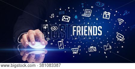 hand holding wireless peripheral with FRIENDS inscription, social media concept