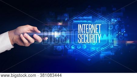 hand holding wireless peripheral with INTERNET SECURITY inscription, cyber security concept
