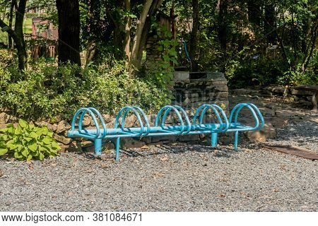 Blue Metal Bike Rack In Gravel Lot In Front Of Trees In Recreational Forest Park.