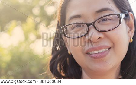 Close Up Face Of Asian Middle Aged Woman With Eyeglasses In A Park, Happy Feeling, Image Against Lig