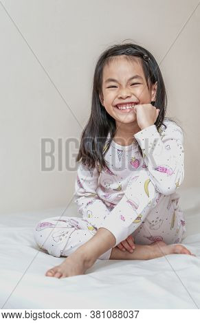Happy And Healthy Asian Child Girl Sitting On White Bed, Soft Brown Wall Background. Happy Cute Face