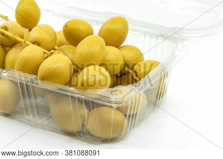 Close Up Fresh Date Palm Fruit Or Date Fruit In Cleared Plastic Box Or Container For Sell On White B
