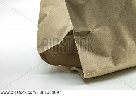 Close Up Large Hole At The Bottom Of The Bag, Brown Paper Bag With Damage Hole On White Background.