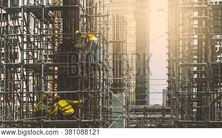Asian Construction Workers Installing Concrete Pillar For Building Construction With Metal Rebar Rod