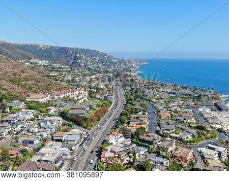 Aerial View Of Main Road Crossing Laguna Beach Coastline Town With Houses On The Hills And Pacific O