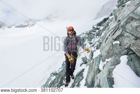Male Alpinist In Sunglasses And Safety Helmet Holding Fixed Rope While Climbing Snowy Mountain. Moun