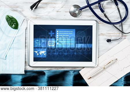Laboratory Patient Examination In Doctors Office. Tablet Computer With Medical App Interface On Scre