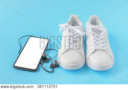 Mockup Image. Sneakers And Phone. Mobile Phone With A Blank Screen, White Sneakers On Blue Backgroun