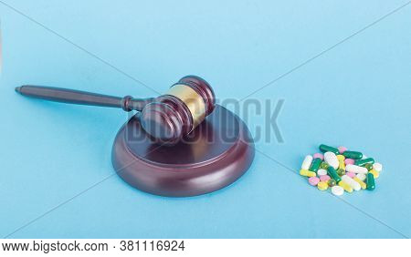 A Pile Of Pills And A Judicial Gavel On A Blue Background. The Concept Of Substandard Pills And Coun