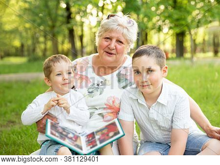 Grandmother With Grandchildren Enjoying Time Together In Spring Nature, Relaxing On The Grass. Grand