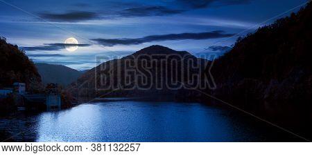 Panorama Of Tarnita Lake In Romania At Night. Beautiful Nature Scenery In Autumn In Full Moon Light.