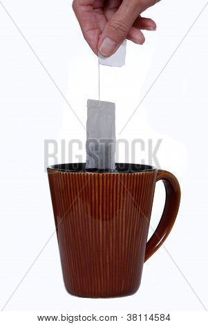 Hand Holding Teabag Above Ceramic Mug.