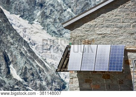 Close Up Of Blue Solar Panels On Wall Of Brick House In Snowy Mountains In Switzerland. Special Equi