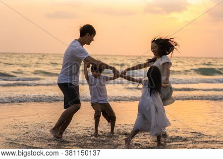 Asian Young Happy Family Enjoy Vacation On Beach In The Evening. Dad, Mom And Kid Relax Playing Toge