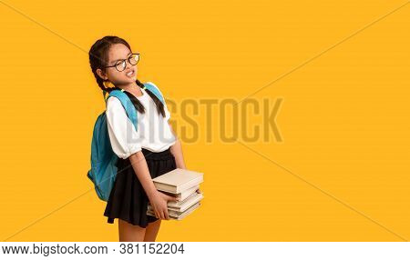 Too Much Homework. Discontented Asian School Girl Carrying Heavy Books Over Yellow Studio Background