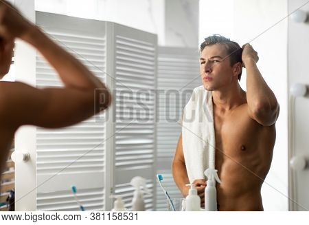 Focused Man Looking In Mirror Putting Wax Touching His Hair Styling Or Checking For Hair Loss Proble