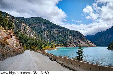 Road Along The Turquoise Mountain Lake Carpenter In Autumn. Mountains With Coniferous Forest Around