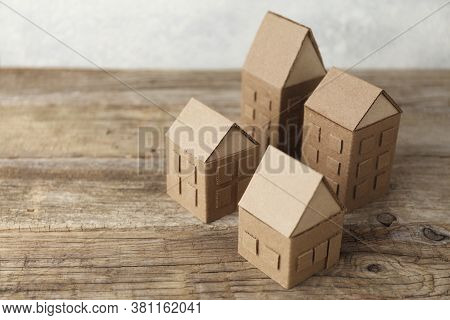 Cardboard Toy Houses On Wooden Background. Sale Or Rental Of Housing. Neighbors In House. Comfortabl