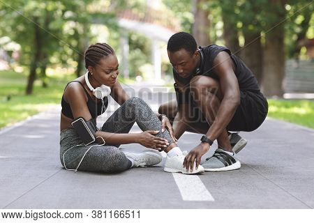 Jogging Injuries. Caring Black Guy Helping Girlfriend Suffering From Sprained Ankle Trauma During Ru