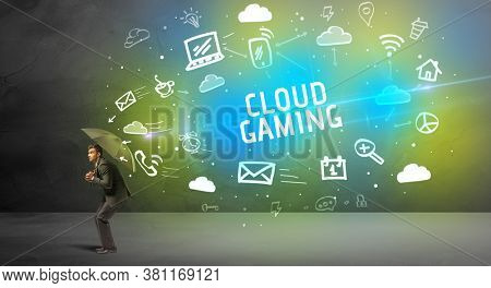 Businessman defending with umbrella from CLOUD GAMING inscription, modern technology concept