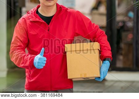 Close Up Delivery Man Wearing Blue Gloves In Red Cloth Holding A Box Package