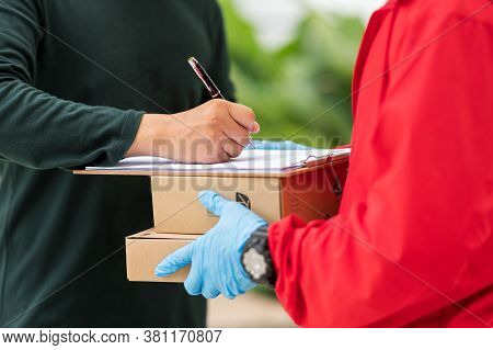 Male Customers Are Signing To Sign For Delivery From Delivery Man.