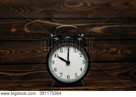 Clock On A Wooden Background. The Clock Shows The Time Of Ten O'clock In The Afternoon. Clock Showin