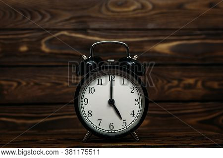 Clock On A Wooden Background. The Clock Shows The Time Of Five O'clock In The Afternoon. Clock Showi