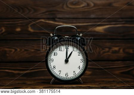 Clock On A Wooden Background. A Clock Showing The Time Of One O'clock. Clock Showing The Time Of One