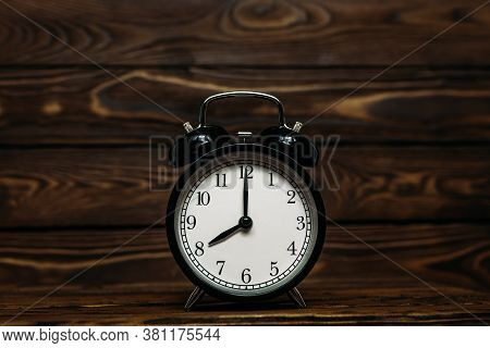 Clock On A Wooden Background. The Clock Shows The Time Of Eight O'clock In The Afternoon. The Clock