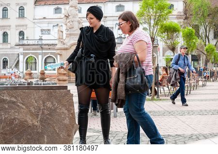 Timisoara, Romania - April 13, 2016: Two Women Looking At A Sculpture On The Street. Real People.