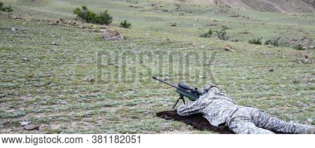Shooter In Camouflage Before Firing A Rifle With A Telescopic Sight. The Sniper Is Preparing For Acc