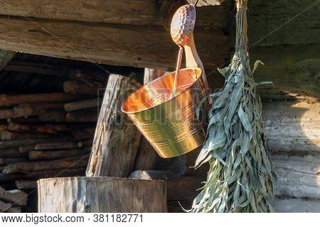 Sauna Equipment Background Of Wet Copper Bucket, Ladle And Bathing Eucalyptus Broom Hanging In Front