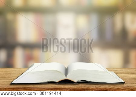Education Concept : Opened Book With Blank Page On Wooden Table With Blurry Image Of Library In Back