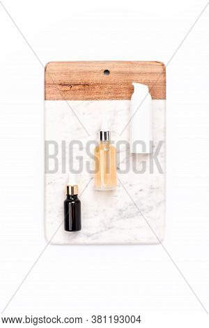 Glass And Plastic Bottles Of Essence Or Serum And With Chamomile Flowers