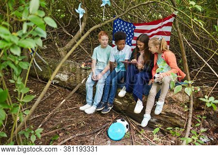 Multi-ethnic Group Of Kids Using Digital Tablet While Playing In Yard Hiding Under Bushes With Ameri