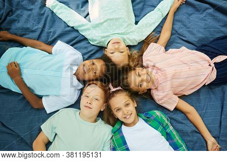 Top View At Multi-ethnic Group Of Kids Lying In Circle On Blanket Outdoors And Looking At Camera
