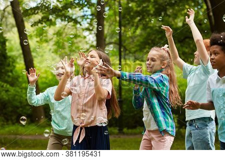 Waist Up Portrait Of Multi-ethnic Group Of Carefree Children Running In Park While Playing With Bubb