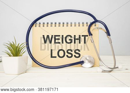 The Word Weight Loss Is Written On A Chalkboard With A Stethoscope On A Wooden Background. The Conce