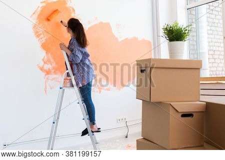 Cheerful Woman Painting The Walls Of New Home. Renovation, Repair And Redecoration Concept.