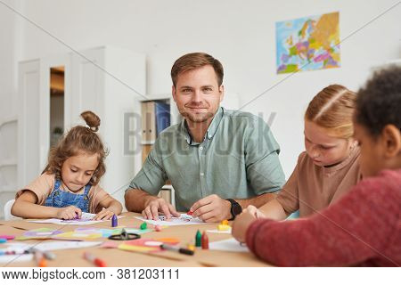 Portrait Of Male Teacher Smiling At Camera While Working With Multi-ethnic Group Of Children Drawing