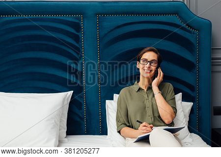 Mid Adult Woman Lying On A Bed In Hotel Room Talking On Mobile Phone And Looking Away