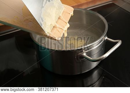 Cooking Spaetzle, Homemade Egg Pasta Dough Is Scraped From A Wooden Board Into Boiling Water, Typica